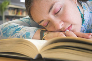 Beautiful student sleeping over a book on the libray.